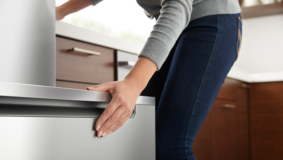 Woman Opening Freezer on Stainless Steel Bottom Freezer Refrigerator