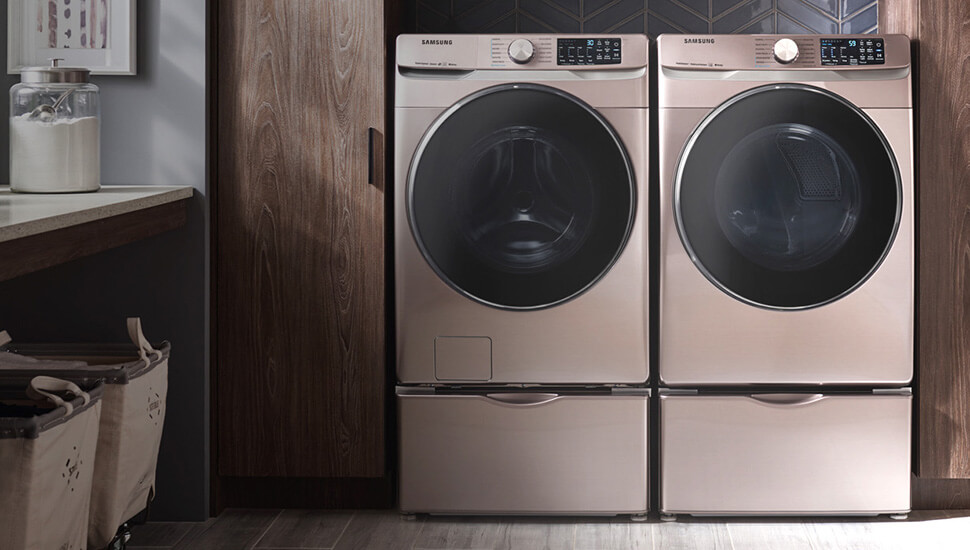 champagne front load washer and dryer on pedestals