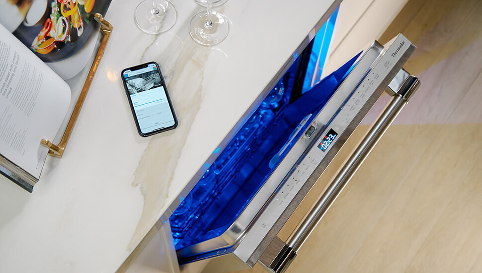 open Thermador dishwasher displaying blue lit interior